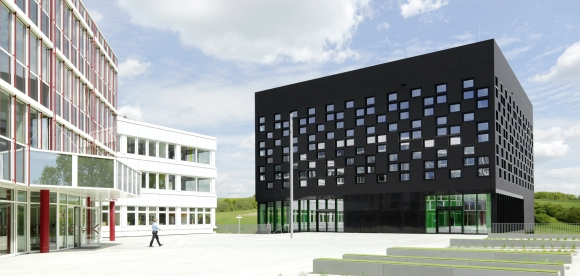 The black, cube-shaped new building has a so-called pixel facade, which is created by a multitude of small, staggered windows.